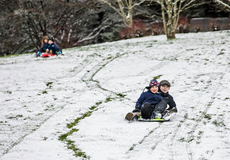 (Image is Clickable Link) Wilco Richards and Thomas Johnson enjoy a snowy day off with some sledding in Washington Park.
