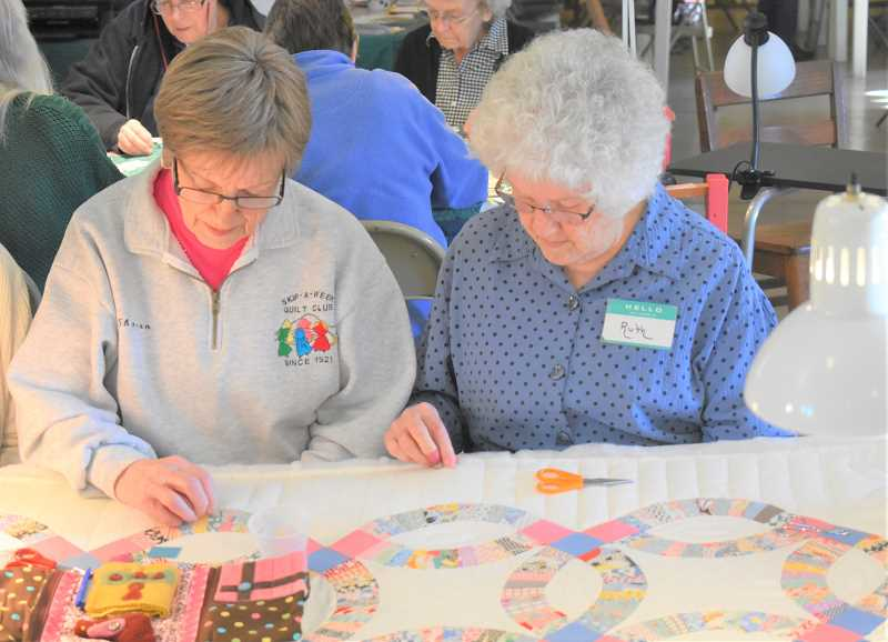 ESTACADA NEWS PHOTO: EMILY LINDSTRAND - Garfield Skip-a-Week Club members Sharon Young and Ruth Lazott work on a quilt during a recent meeting of the group.