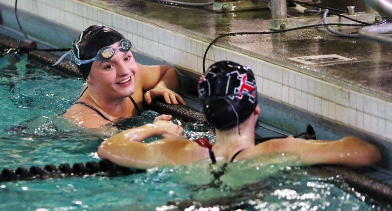 TIMES PHOTO: DAN BROOD - Tigard senior Kaitlyn Wornath (left) smiles as she talks to Tualatin's Isabelle Ehming following the finish of the 50-yard freestyle. Wornath won in a time of 26.43.
