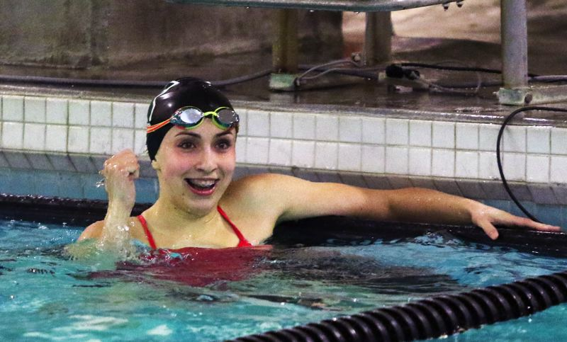 TIMES PHOTO: DAN BROOD - Tigard sophomore Jaime Cavalli smiles after her come-from-behind victory in the 100-yard backstroke event during the Tigers' meet with Tualatin.
