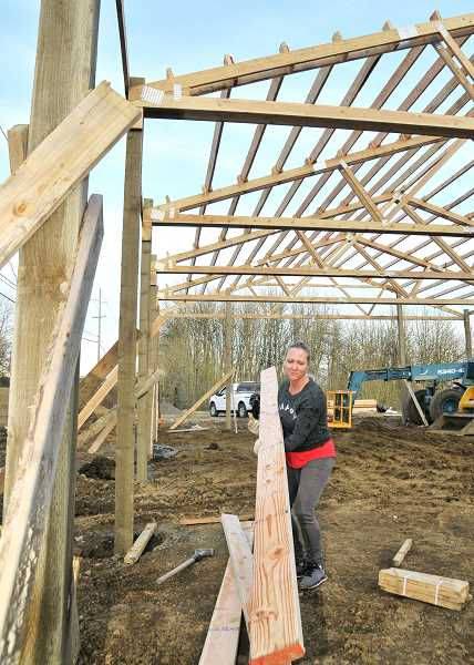 GARY ALLEN - Danielle Burk hoists some lumber as the couple continues construction of Odin's Beard Meadery at the intersection of Highway 99W and Riverwood Road west of Dundee.