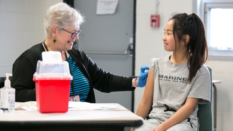 COURTESY PHOTO: MULTNOMAH COUNTY - Jennifer Tujo, an on-call nurse with Multnomah County, gets a student ready for a vaccination.