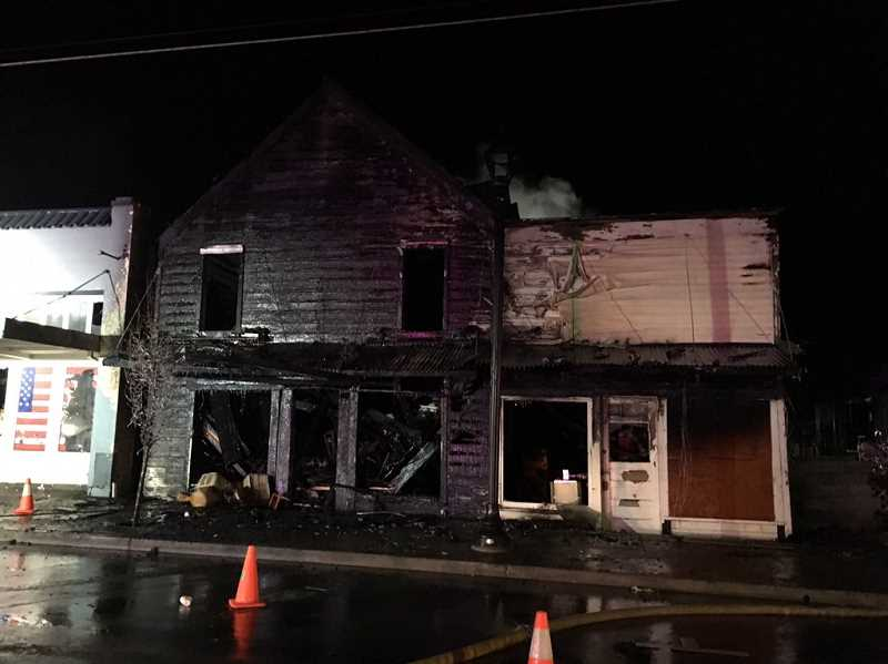ELISE HAAS - A Wednesday night fire in downtown Molalla gutted the old boutique building and damaged the feed store next door. A woman got out of the building safely, but the whereabouts of her son are still in question.