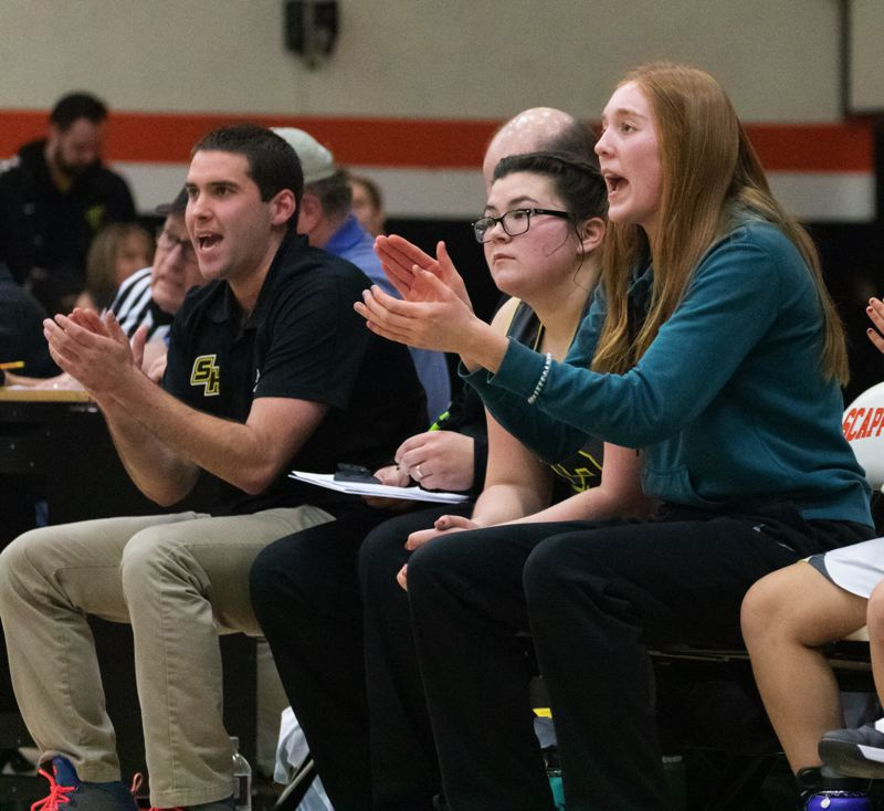 COURTESY: LOREN WOHLGEMUTH - St. Helens coach Michael Fendall (left) and injured star Maddie Holm (right) cheer on the Lions in their Tuesday game at Scappoose.