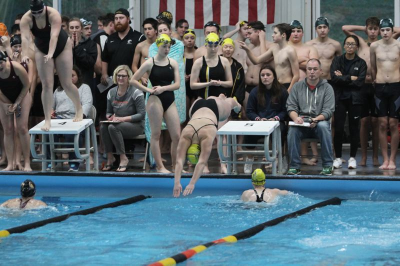 SPOTLIGHT PHOTO: MILES VANCE - The St. Helens girls 200 medley relay has Olive Owens diving in as Maggie Wheeldon finishes her leg and Molly Wheeldon and Audra Lein watch at the side of the pool.
