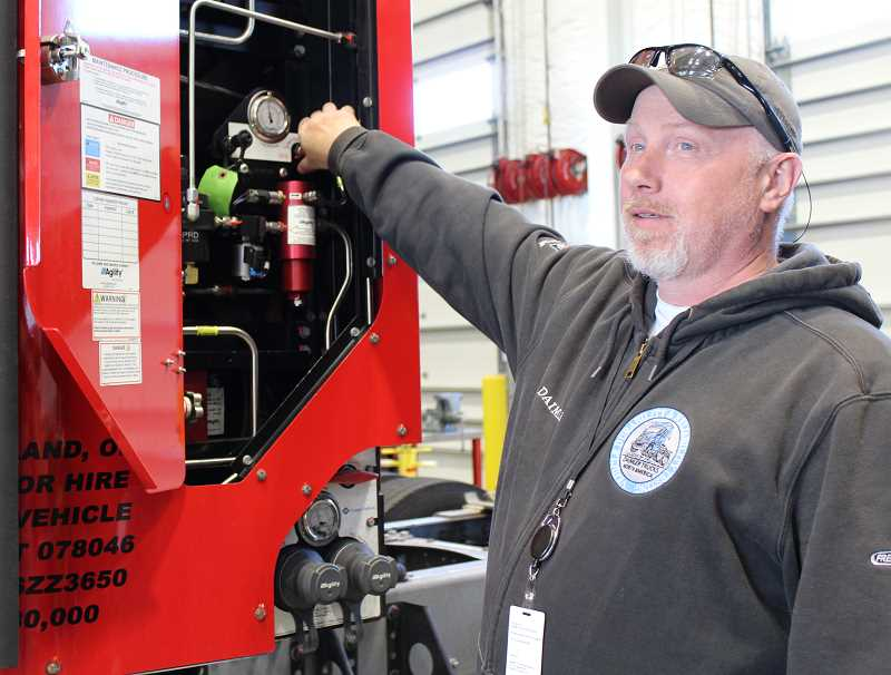 HOLLY M. GILL/MADRAS PIONEER - Robert Hansen, operations manager at the Madras facility, displays controls on a Cascadia truck, which runs on compressed natural gas.