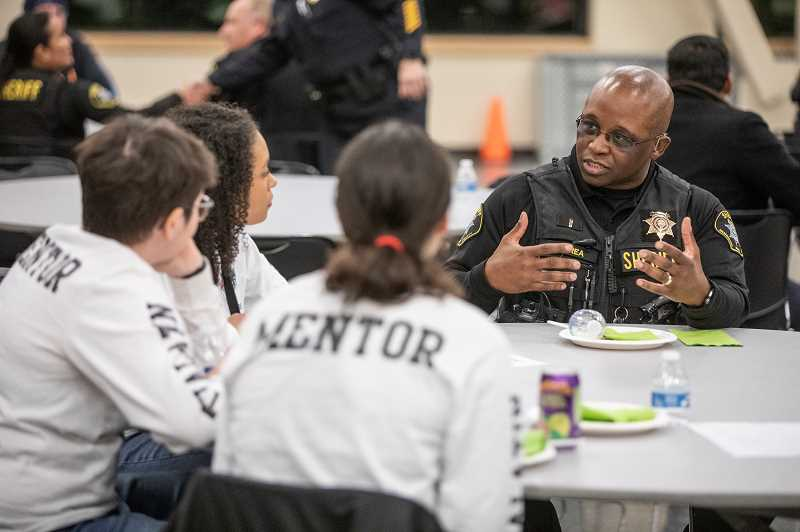 TIMES PHOTO: JONATHAN HOUSE - Washington County Lt. Erroll McCrea talks with Tigard High mentors during the No Hate Zone Community Dinner.