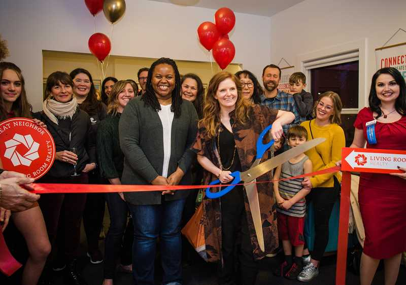 PHOTO BY 22PAGES - Living Room Realty founder Jenelle Isaacson wields the scissors for the ceremonial ribbon cutting at the firm's new Multnomah Village location on Friday, Feb. 1.  To her right is Anika Stephen Wilbur, assistant  managing principal broker.