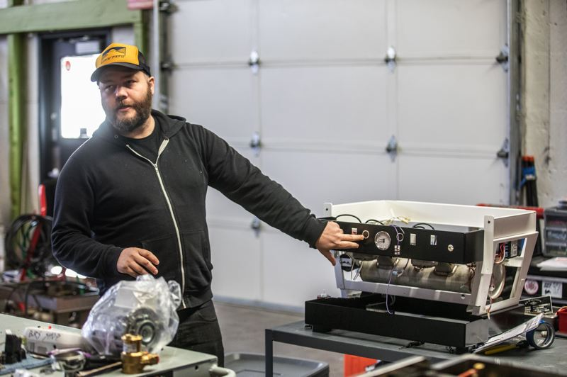 PAMPLIN MEDIA GROUP: JONATHAN HOUSE - Double J at a machine that Black Rabbit was working on for a client. As well as sell and install commercial espresso machines, they customize, service and maintain them, and teach classes in making coffee.