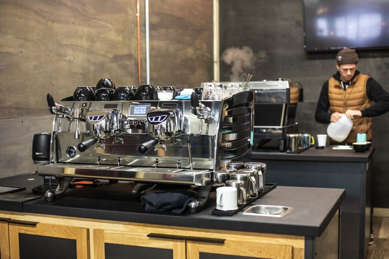 PAMPLIN MEDIA GROUP: JONATHAN HOUSE - Staff member David George prepares to make a latte at Black Rabbit Coffee on the in-house La Marzocco worth $16,000. In the foreground is a $24,000 Victoria Arduino Black Eagle superautomatic. The company also teaches milk steaming and latte art, because thats what people see on Instagram, and thats what people ask for.