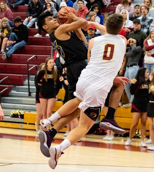 LON AUSTIN/CENTRAL OREGONIAN - Kevin Sanchez is fouled by Redmond's Henry Chambers late in the first quarter of the Cowboys' loss to the Panthers. Sanchez made both free throws and scored 21 points in the game, but the Cowboys fell to 1-4 in Intermountain Conference play.