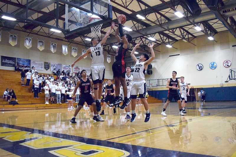 HERALD PHOTO: TANNER RUSS - Oregon City's Erich Nova goes up for a basket against the swarming Canby defense. The Pioneers defeated the Cougars 55-35.