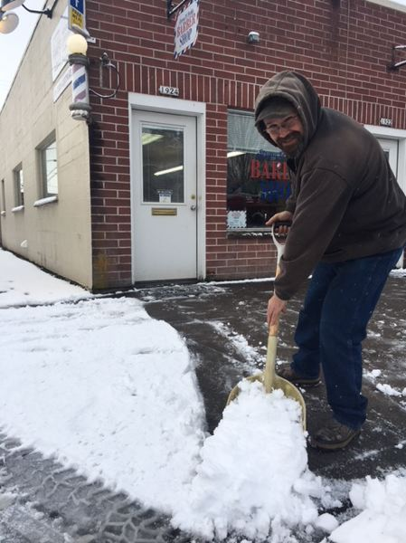 CONTRIBUTED PHOTO - Chris Mohonich, whose dad, Rudy, owns Sirena & Rudy's Barbershop, shoveled snow in front of the downtown Forest Grove salon Saturday morning.