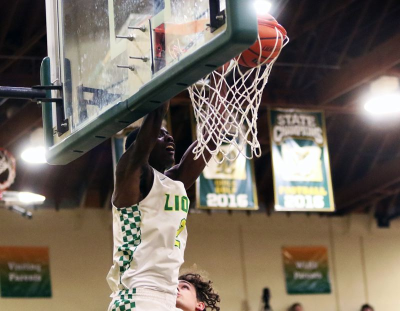 TIMES PHOTO: DAN BROOD - West Linn senior Oreon Courtney slams down the first of his two dunks during the Lions' Three Rivers game with Tualatin on Friday.