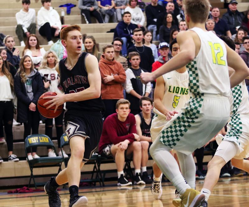 TIMES PHOTO: DAN BROOD - Tualatin senior Jack Rose (left) looks to drive the baseline during the Wolves' win at West Linn on Friday.