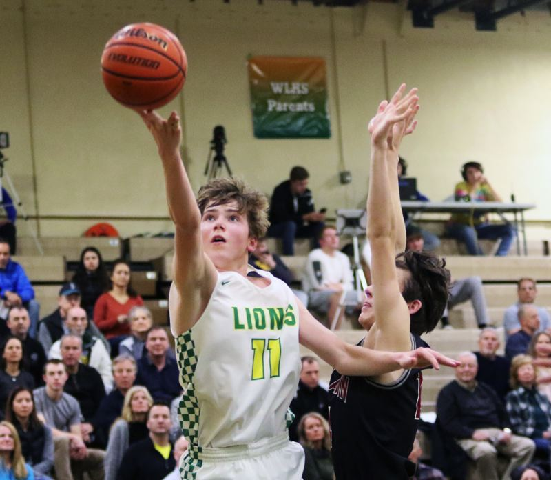 TIMES PHOTO: DAN BROOD - West Linn junior Gus Michelon goes up to the basket during the Lions' game with Tualatin on Friday. Michelon led West Linn with 14 points.