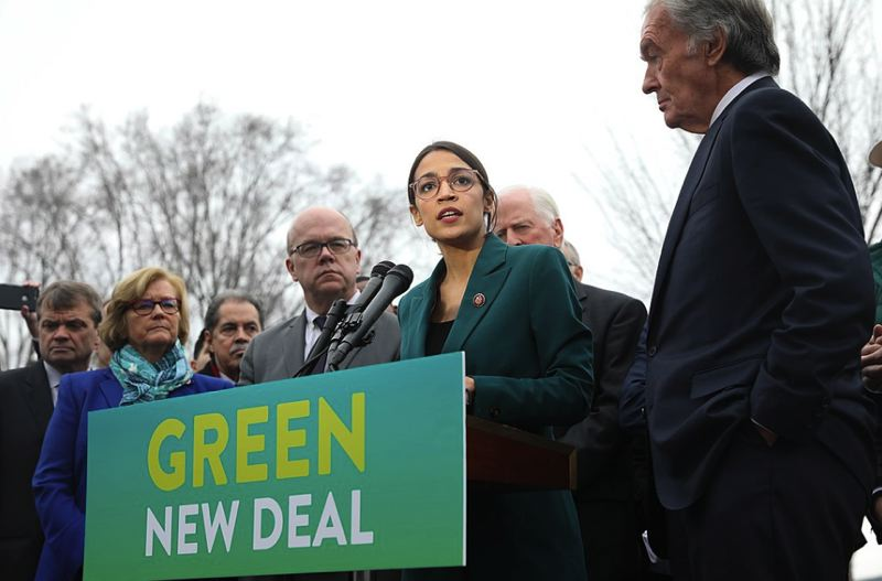 VIA WIKIPEDIA - Rep. Alexandria Ocasio-Cortez, center, speaks about the Green New Deal in front of the Capitol Building on Feb. 7.