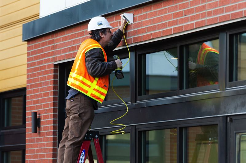 STAFF PHOTO: CHRISTOPHER OERTELL - A construction worker installs a camera at Cornelius Place on Friday, Jan. 25.