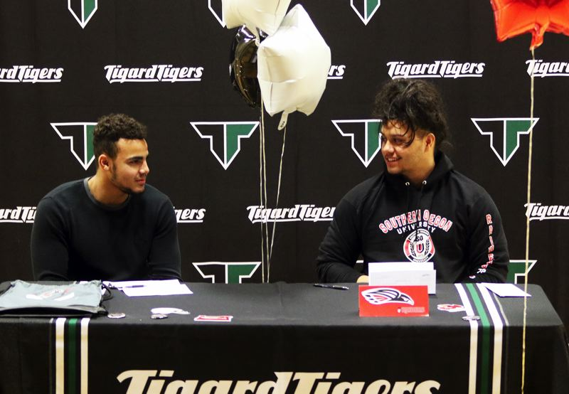 TIMES PHOTO: DAN BROOD - Tigard High School seniors Noah Jackman (left) and Isaia Tavita Porter signed their national letters of intent to play football at Southern Oregon University.