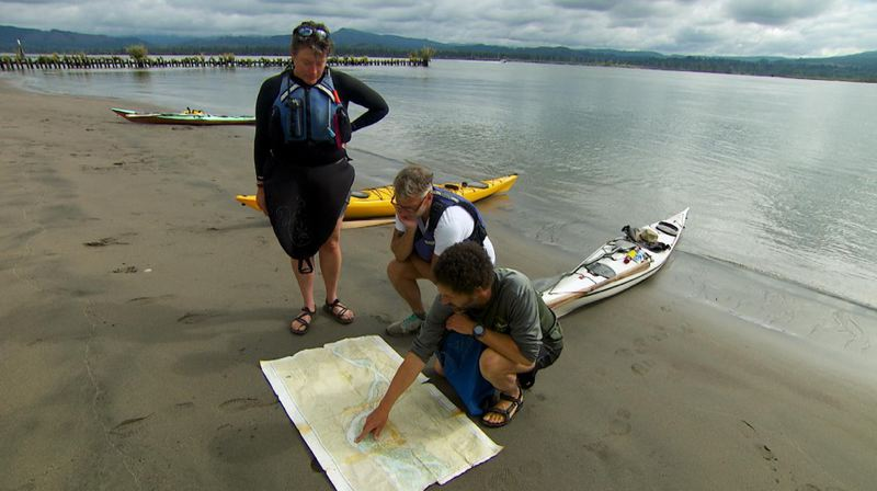 COURTESY NICK FISHER, OPB - Andrew Emlen, Chris Hathaway and Kyleen Austin study maps on the shore of Lark Island, a sandy dredge spoil east of Tenasillahe Island.