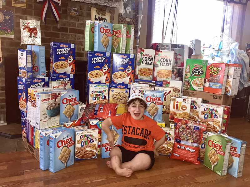STAFF PHOTO: EMILY LINDSTRAND - Bryton Figgins, a student at Estacada High School and one of last years Pamplin Media Group Amazing Kids, sits among the numerous boxes of breakfast cereals she collected and donated to a nonprofit that creates an inclusive environment for people with disabilities.