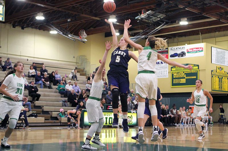 PAMPLIN MEDIA GROUP PHOTO: MILES VANCE - Canby freshman Joey Baguio lofts a shot toward the basket during her team's 75-51 loss to West Linn at West Linn High School on Tuesday night.