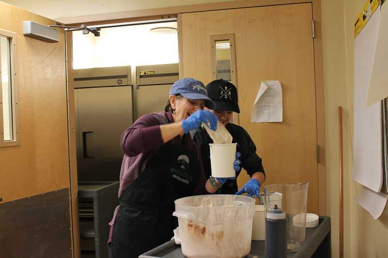 SPOKESMAN PHOTO: HOLLY BARTHOLOMEW  - A Junior Scoop worker and volunteer pack ice cream into containers for customers to take home.
