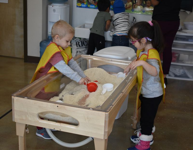 STAFF PHOTO: TERESA CARSON - Two Head Start kids are busy in the rice sensory bin, building and measuring. The two little guys in the background wash their hands after their turn, at a sink sized just right for preschoolers.