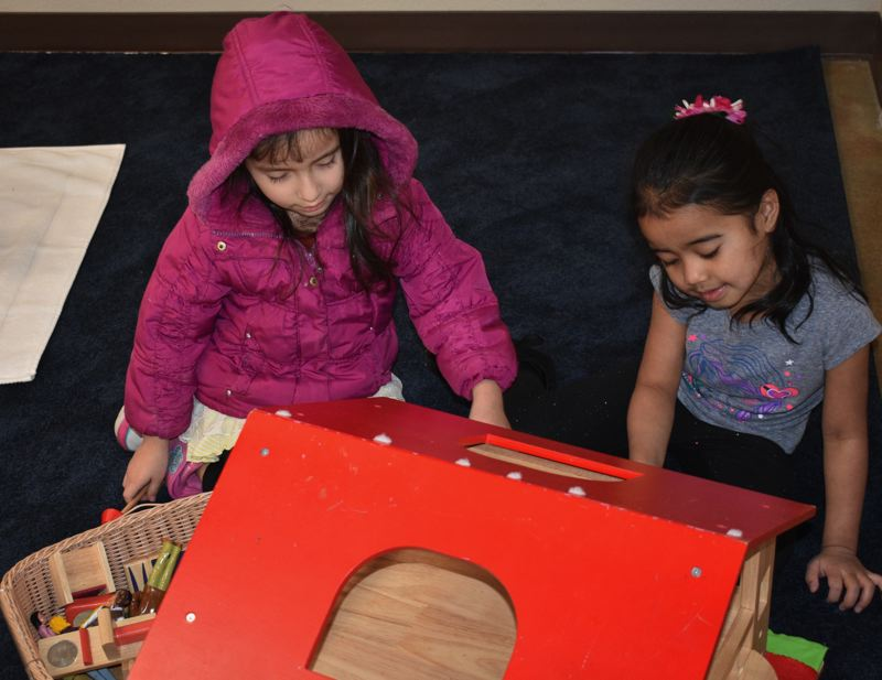 STAFF  PHOTO: TERESA CARSON - These two young ladies are setting up the miniature house. It's always difficult to decide what goes where.