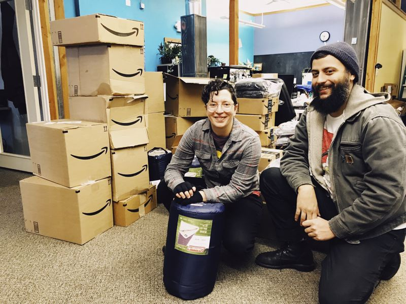 CONTRIBUTED - JOIN Outreach Workers Rebecca Fry and Fernando Peña kneeled on Monday at the nonprofit's Northeast Portland offices near a stack of donations for the local homeless that were purchased through Amazon.