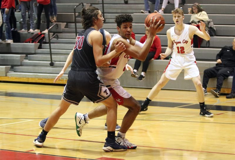 PAMPLIN MEDIA: JIM BESEDA - Oregon City's Erich Nova takes the ball to the basket around Tualatin's Bridger Steppe in the first half of Tuesday's 48-33 Three Rivers League home win. Nova led all scorers with 17 points.