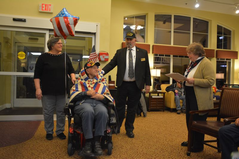 SPOTLIGHT PHOTO: COURTNEY VAUGHN - Bill Leanna (seated) is honored with a Quilt of Valor for his 93rd birthday at Brookdale Rose Valley Senior Living in Scappoose. Pictured with Leanna: Northwest Quilters QOV volunteers Maria Fenstermaker, Robert Eldred, and Maureen Orr Eldred.