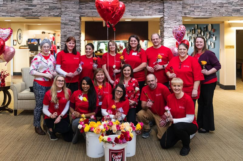 STAFF PHOTO: CHRISTOPHER OERTELL - Employees from Marquis Forest Grove volunteered to come in and pass out roses and share messages of love to seniors they help care for each day.