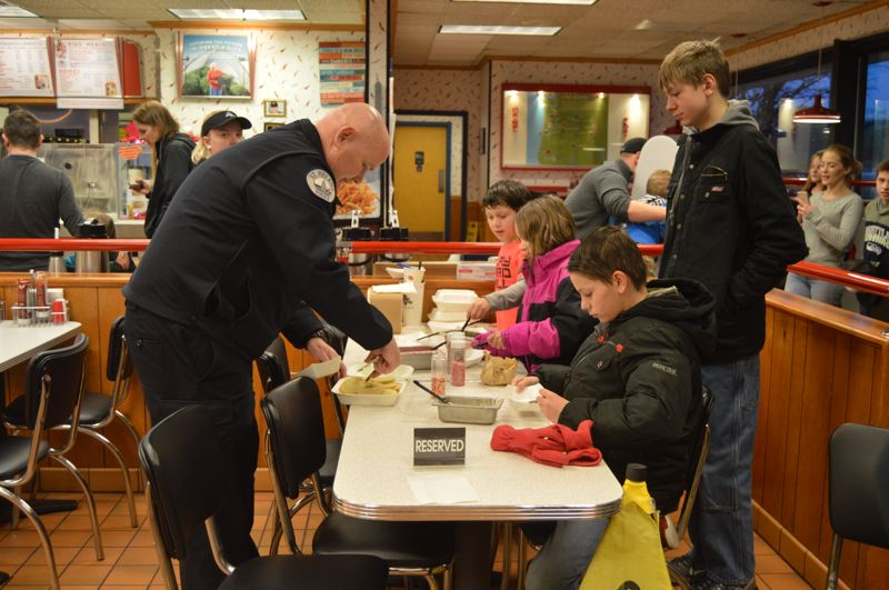 SPOTLIGHT PHOTO: NICOLE THILL-PACHECO - St. Helens Police Chief Brian Greenway, left, hands out cookies to a group of children waiting to frost and decorate their Valentines Day cookies.