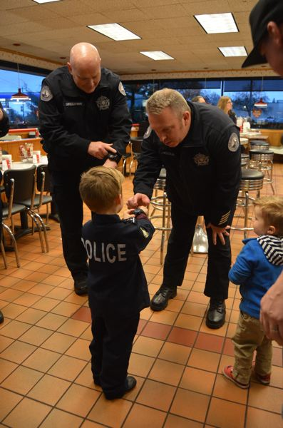 SPOTLIGHT PHOTO: NICOLE THILL-PACHECO - Camden Prasch, 4, dressed in his very own police officer uniform. Here he shows off his watch to SHPDs Chief Brian Greenway and Lt. Joe Hogue.