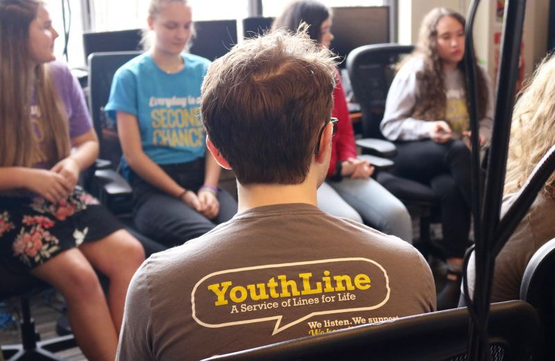 TRIBUNE PHOTO: ZANE SPARLING - Student volunteers at YouthLine share their experiences helping peers with mental health issues at the Lines for Life office on Friday, Feb. 15.