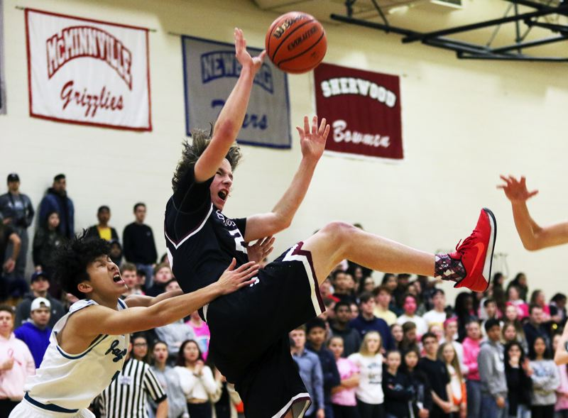 TIMES PHOTO: DAN BROOD - Sherwood senior post Charlie Bulfinch (right) is fouled by Century junior Ikan Chan as he goes to the basket on a fast break during Friday's game. The Bowmen got a 66-49 victory.