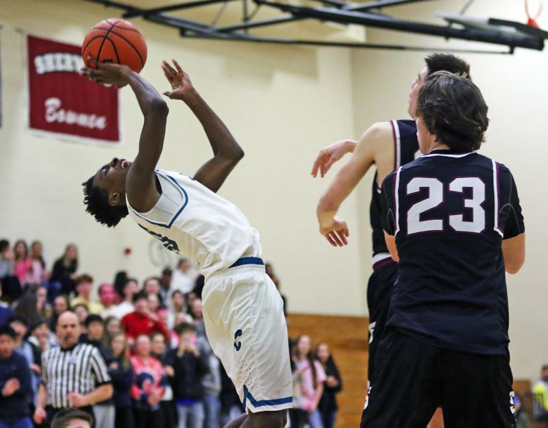 TIMES PHOTO: DAN BROOD - Century sophomore guard Edy Essien (left) is fouled as he goes up for a shot during the Jaguars' game with Sherwood on Friday.