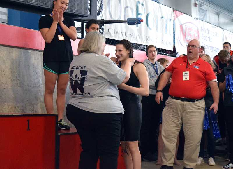 SPOKESMAN PHOTO: TANNER RUSS - Swim coach Deb Mandeville places Maozs first place medal around her neck before she takes the podium.