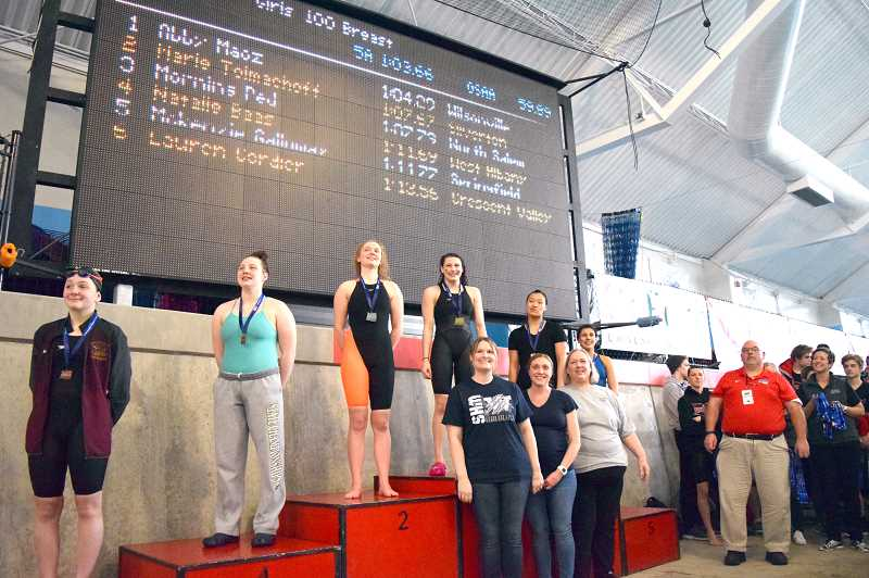 SPOKESMAN PHOTO: TANNER RUSS - Wilsonvilles Abby Maoz stands on the podium after claiming first place in the 100 breaststroke.