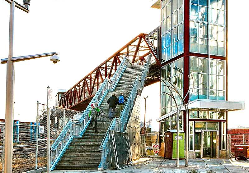 DAVID F. ASHTON - With construction fences pulled back, pedestrians use the stairs of the TriMets Rhine-Lafayette Pedestrian Overpass; an elevator tower is at right.