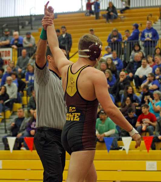 STAFF PHOTO: WADE EVANSON - Forest Grove's Gavin Rice raises his hand in victory following his semifinal win at the Pacific Conference District Championships, Feb. 15-16, at Forest Grove High School. Rice placed second in the 182 pound division.