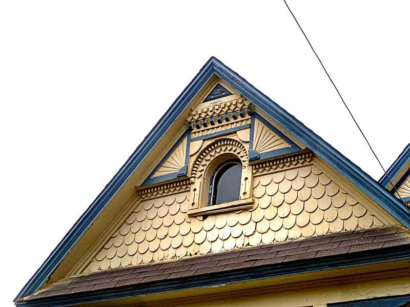 EILEEN G. FITZSIMONS - A close-up view of the front gables, which display typical details of the style, with patterned shingles and richly detailed millwork.
