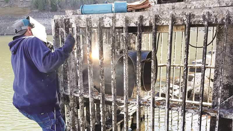 PHOTO COURTESY OF OCHOCO IRRIGATION DISTRICT - Ochoco Irrigation District staff weld flanges onto the trash rack at the base of the intake tower of Ochoco Dam. Low water levels brought on by poor snowpacks and dry weather exposed the work area, making the upgrades possible.