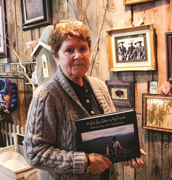 HOLLY SCHOLZ/CENTRAL OREGONIAN   - Diane Dunbar holds the photo book her brother, Rick Fisher, self-published that celebrates dogs and the joy they bring. She is a volunteer at the Humane Society of the Ochocos Thrift Store. Sales from this book benefit the shelter.
