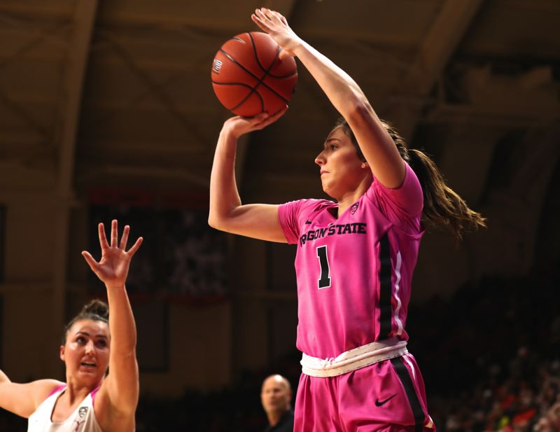 TRIBUNE PHOTO: JAIME VALDEZ - Aleah Goodman (right) of Oregon State launches a 3-pointer before Oregon's Erin Boley can get close on defense during Monday night's 67-62 Beaver victory at Gill Coliseum.