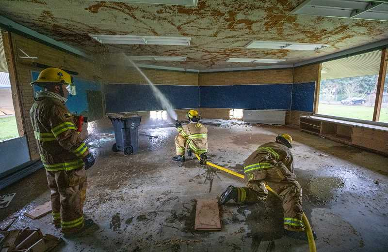 REVIEW PHOTO: JONATHAN HOUSE - Lake Oswego firefighters practice putting out fires in a classroom of the old Bryant Elementary School building.