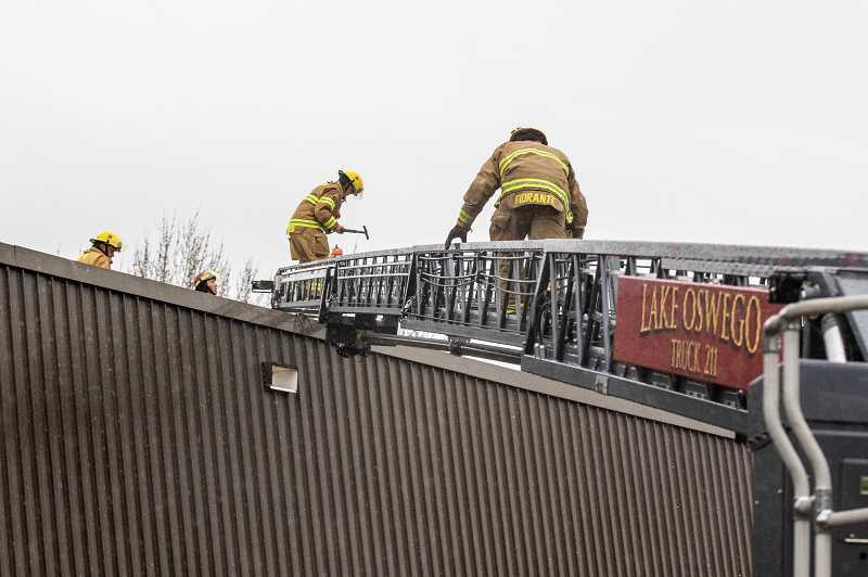 REVIEW PHOTOS: JONATHAN HOUSE - LOFD firefighters practice rescue techniques by scaling the roof of the old Bryant Elementary School building.
