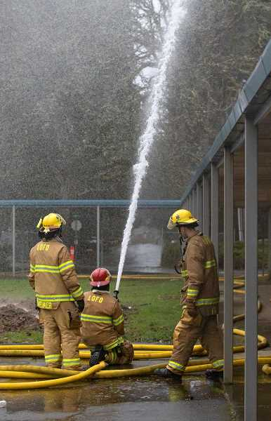 REVIEW PHOTOS: JONATHAN HOUSE - LOFD firefighters practice putting out fires outside of the old Bryant Elementary School building.