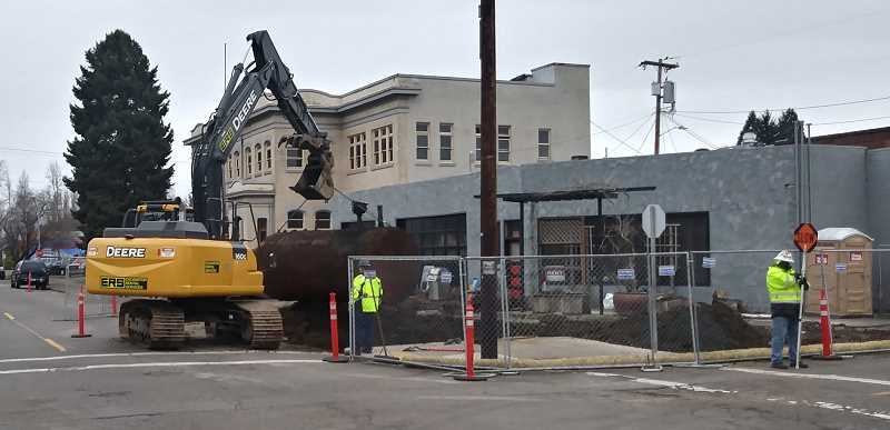 PMG PHOTO: JUSTIN MUCH - Crews remove tank from former gas station on First Street in Woodburn Tuesday, Feb. 19.